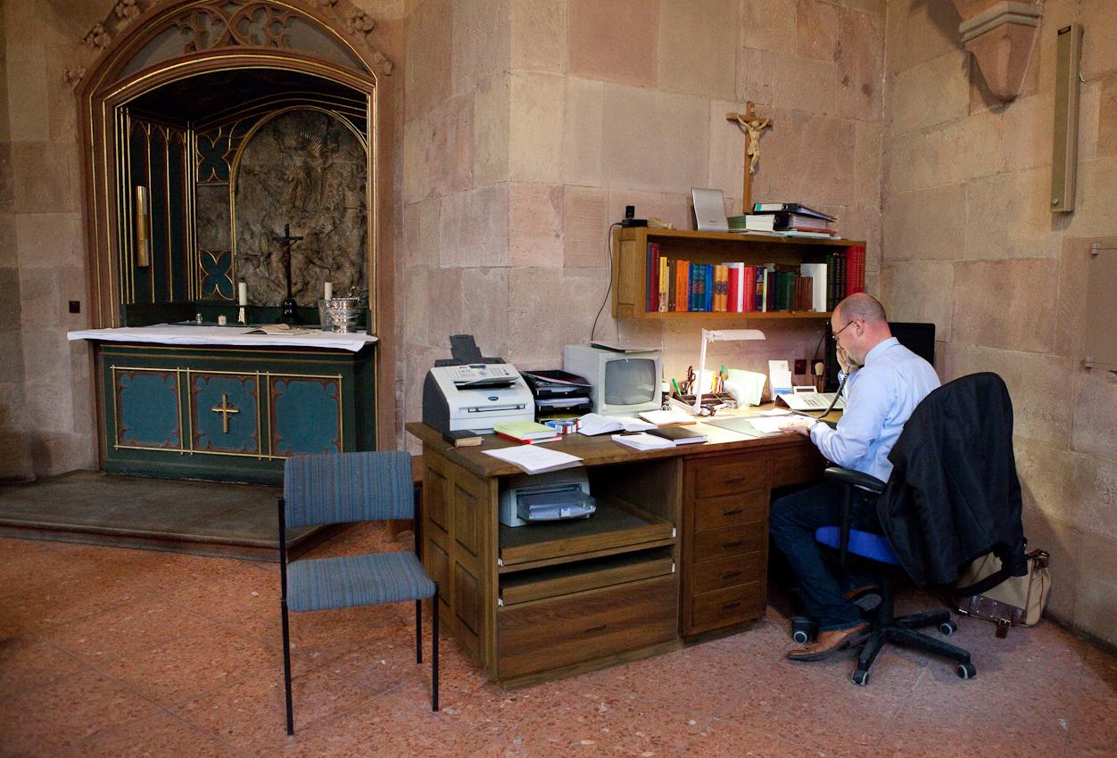 Im Mainzer Dom sitzt Domküster Frank Wiegand an seinem Schreibtisch in der Sakristei und telefoniert, um Details für den abendlichen Gottesdienst abzustimmen.