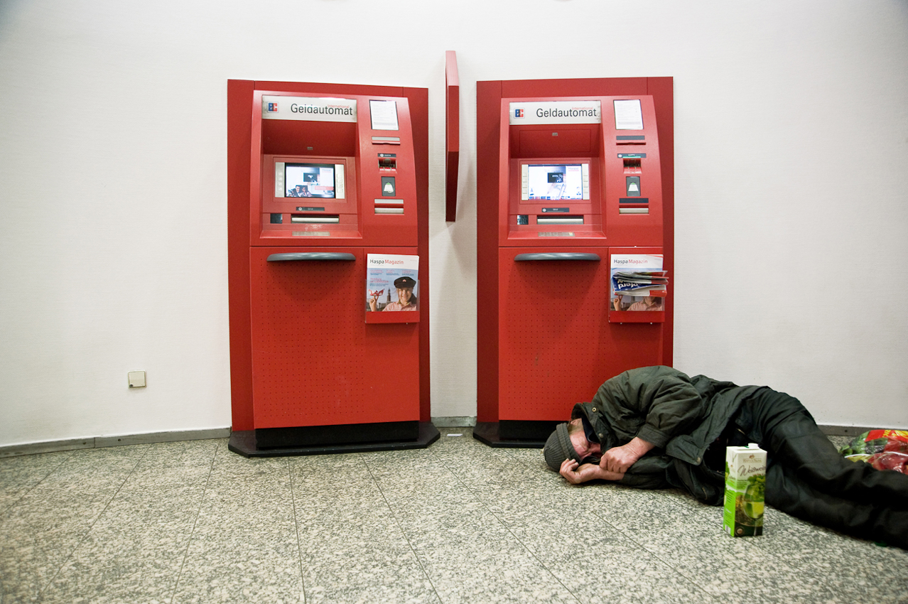 Am Abend, bei kühlen Wetter wärmt sich ein Obdachloser in einer Filiale der Hamburger Sparkasse auf und schäft.