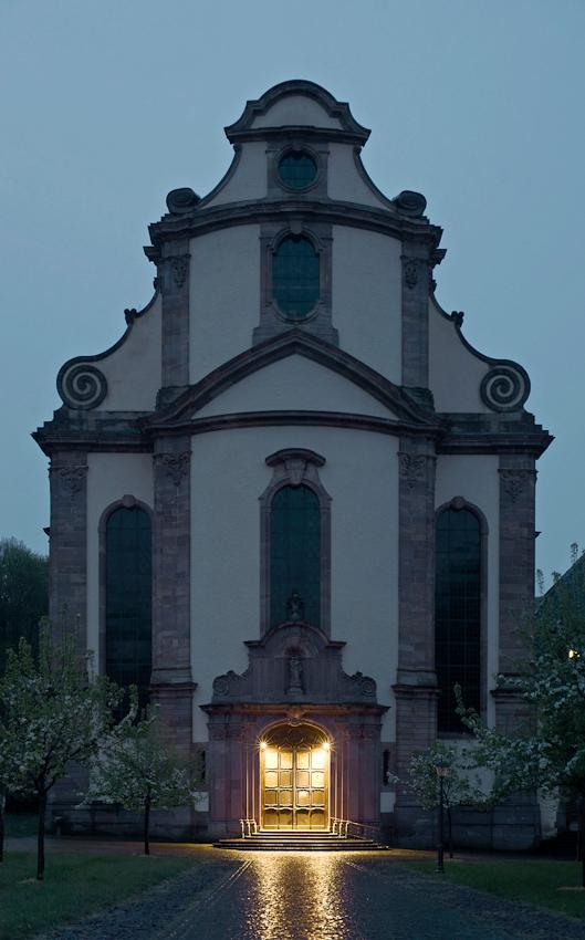 Das Portal der Abtei-Kirche Himmerod in der Eifel leuchtet warm im trüben Licht des Morgens, das hinter der eindrucksvollen Barock-Fassade heraufdämmert.