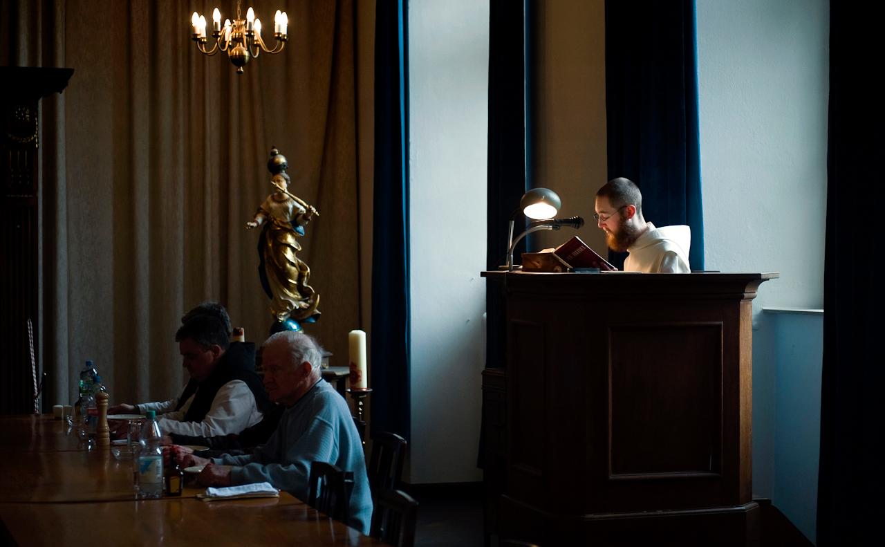 Am Mittag liest Bruder Nathanael (r.) aus der Bibel vor, wäehrend seine Mitbrüder und Patres sowie einige männliche Gäste ihre Mittagsmahlzeit schweigend im Refektorium der Abtei einnehmen.
