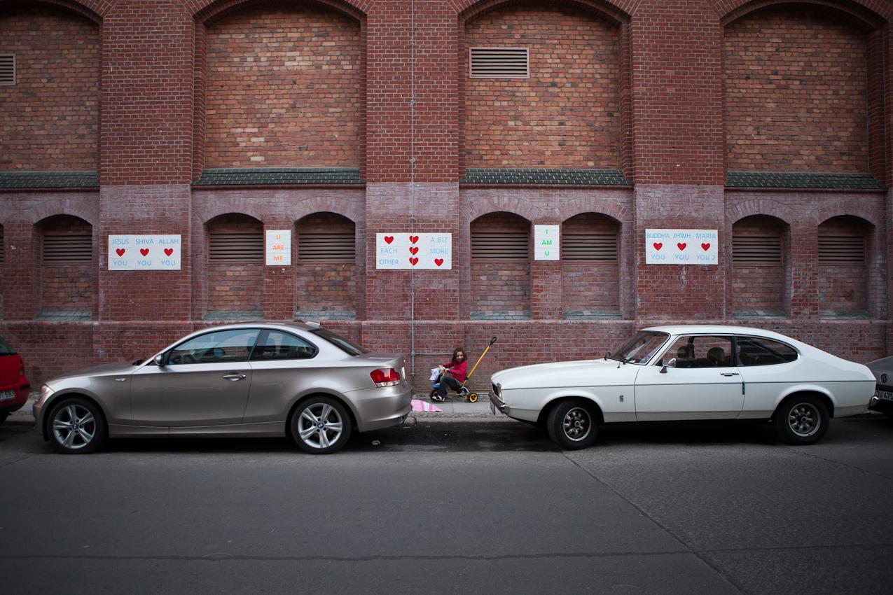 20:27 Uhr, Auguststraße, Berlin-Mitte. Ein kleines Mädchen fährt auf einem Dreirad auf dem Bürgersteig entlag und ist von der gegenüberliegenden Seite im Zwischenraum zwischen zwei parkenden Autos zu sehen. Hinter ihr Straßenkunst.