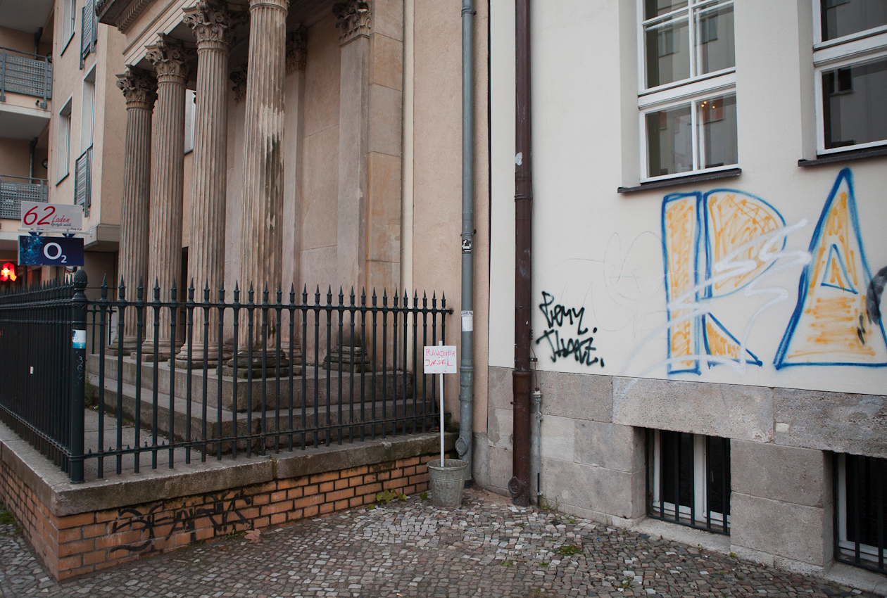 """20:46 Uhr, Koppenstraße, Berlin-Mitte. """"Raucherinsel"""" steht mit Hand geschrieben auf einem Schild, das auf dem Bürgersteig vor einem Zaun neben einer Häuserwand in einem Blecheimer steckt."""