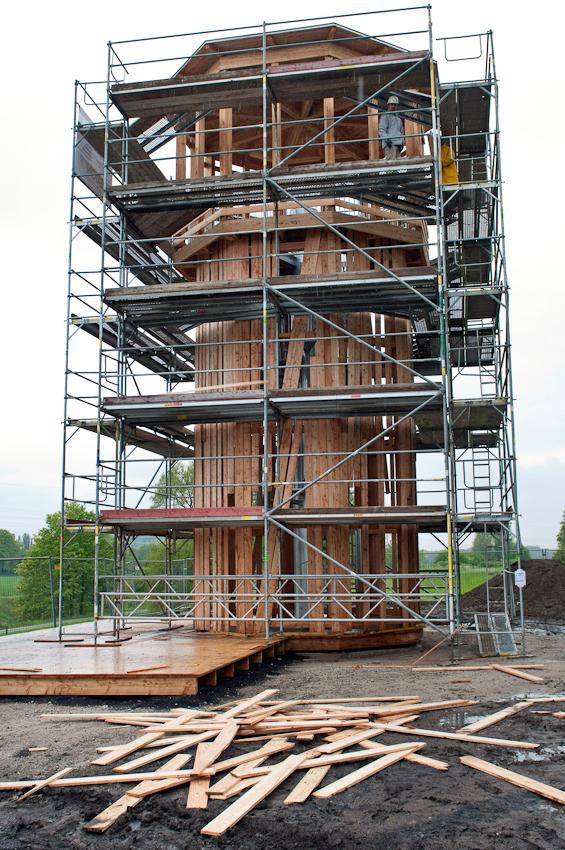 """Der Japaner Tadashi Kawamata stellt mit seinen Assistenten und Mitarbeitern sein Projekt """"Walkway and Tower""""in der Nahe des Wasserkreuzes von Emscher und Rhein-Herne-Kanal, des so genannten Dukers in Castrop Rauxel fertig. Die an den Turm angebrachte Verkleidung aus unbehandeltem Holz tragt ganz bewusst den Charakter des Provisorischen, des Unfertigen und des Verganglichen. Durch das vergangliche Material sind die Arbeiten fragil und thematisieren damit den Prozess des Werdens und Vergehens in der Natur. Kawamata initiiert weltweit Installationen, die in Beziehung zur jeweiligen Umgebung stehen und oft in ihrer architektonischen Struktur einen gewissen Gebrauchswert bzw. eine konkrete Funktion aufweisen.  Ende Mai 2010 wird EMSCHERKUNST.2010, das gro?te Kunstprojekt der Kulturhauptstadt Essen, eroffnet. Dann haben die Besucher 100 Tage Zeit, um die insgesamt acht Ausstellungsraume auf der Emscherinsel zu erkunden.  40 Kunstlerinnen und Kunstler, zum Teil in Duos oder Gruppen arbeitend, erschaffen 20 Werke unterschiedlichster Art."""