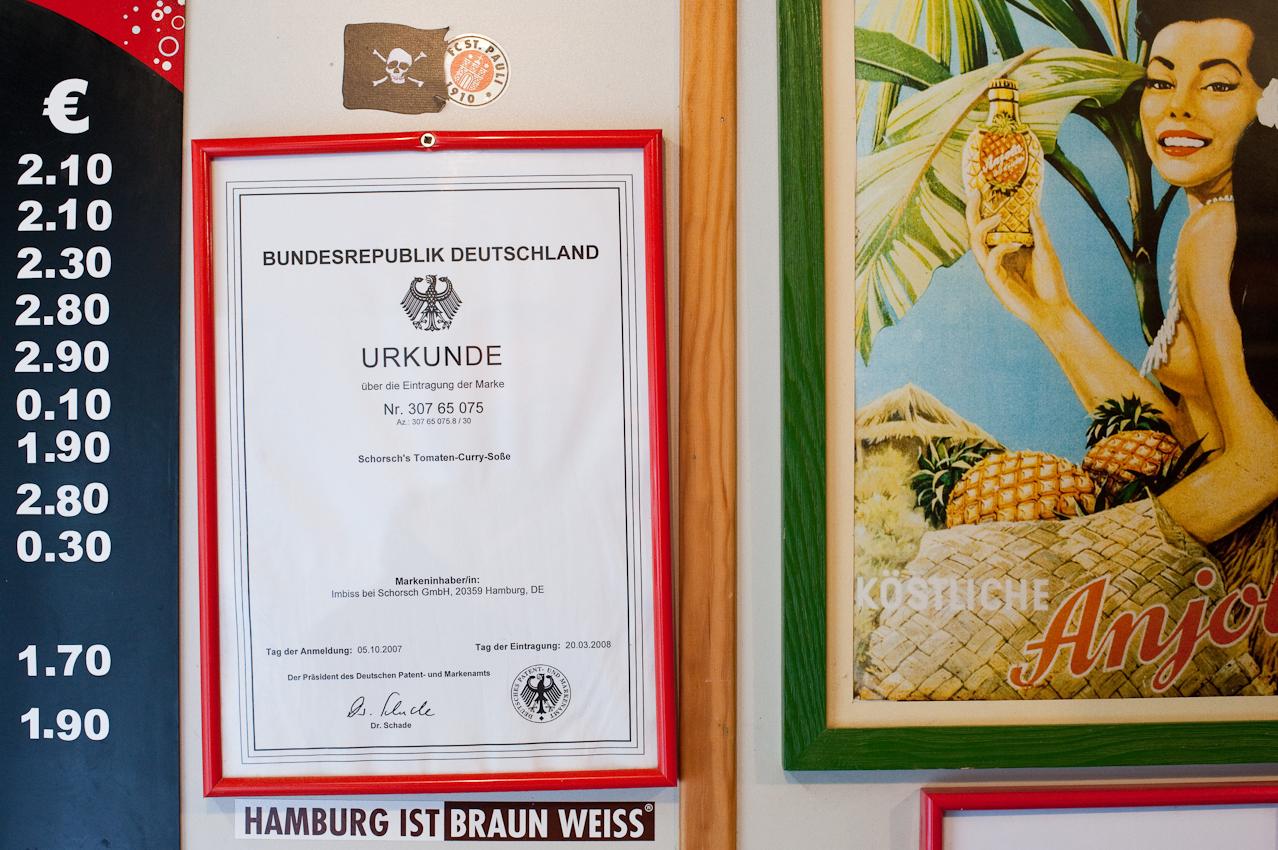Der hausgemachte Ketchup im Imbiss bei Schorsch ist unter dem Namen Schorschs Tomaten-Curry-Sosse als Marke eingetragen. Die Urkunde mit der Nummer 307 65 075 haengt gerahmt an der Wand - zwischen Preisliste und Werbung fuer die Ananas-Limonade Anjola. Aufgenommen im Imbiss bei Schorsch am 07.05.2010 um 15:12, Beim Gruenen Jaeger 14, 20359 Hamburg.