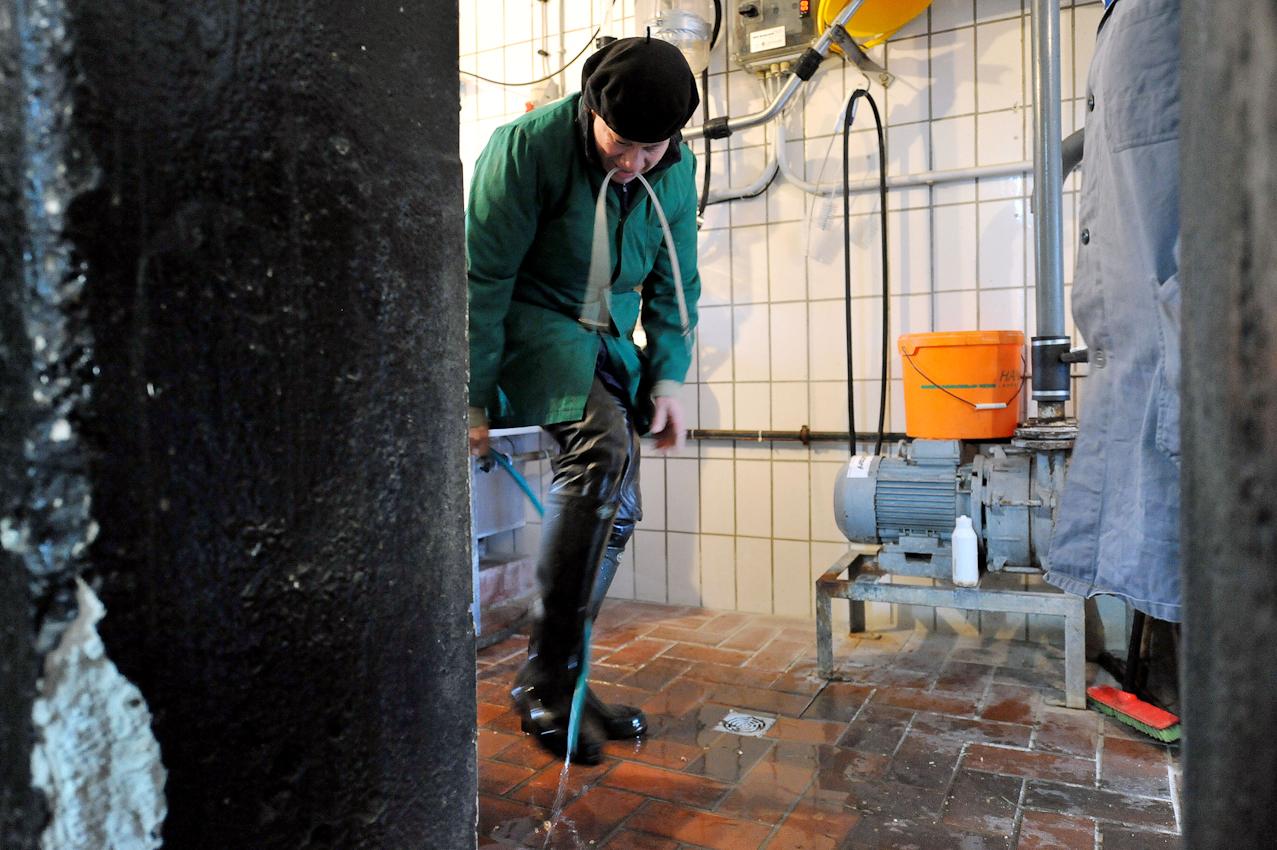 Die Tierärztin Annette Röllmann hat bei dem Landwirt Hans Gustke im niedersächsischen Cluvenhagen (Landkreis Verden) am Freitag (07.05.2010) gegen sieben Uhr morgens eine Milchkuh behandelt. Nach getaner Arbeit spritzt sie ihre Gummistiefel ab, bevor sie sich auf den Weg zum nächsten Patienten macht. Eigentlich wollten die Gustkes ihre Kühe bereits gemolken haben. Nun kam die kranken Kuh dazwischen und der Alltagsbetrieb muss warten. Der Hof Gustke zählt noch zu den alten kleinbauerlichen Vollerwerbsbetrieben, bei dem die gesamte Familie mit anpacken muss.