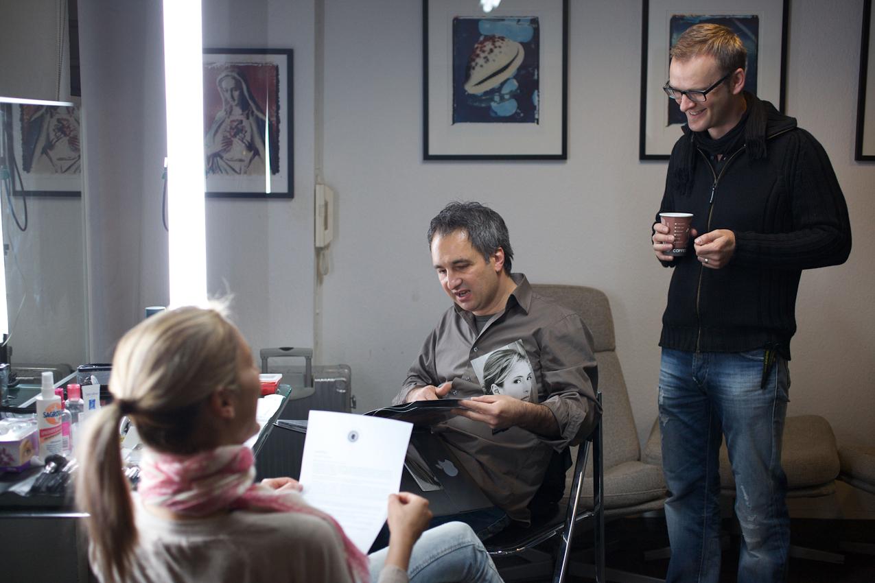 """Ergin Varel Schaut Julias ,,Buch"""" an und hat ihre Setkarte mit dem Unterarm eingeklemmt. Hinter ihm steht Visagist Max (Markus Pavitschitz, www.make-themax-up.com). Julia informiert sich über ,,Ein Tag Deutschland"""""""