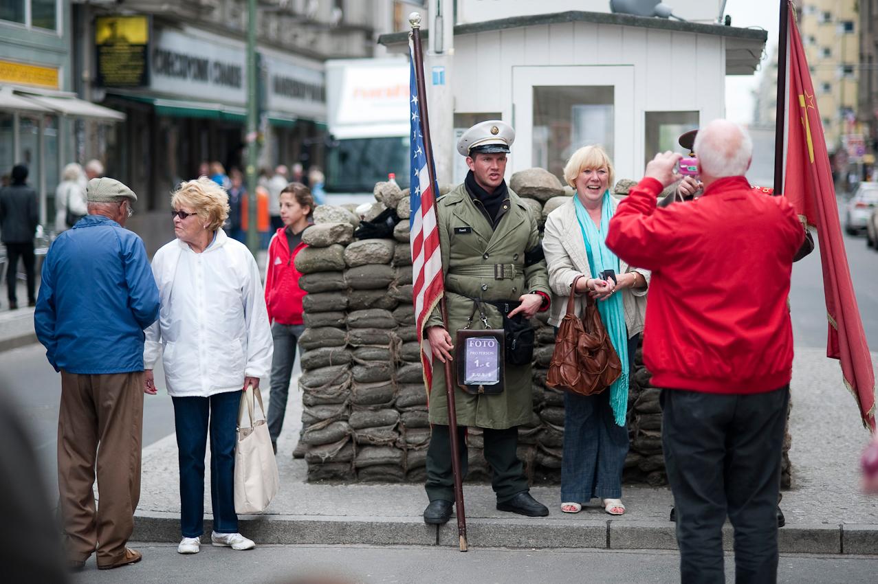 Touristen in Berlin. Checkpoint Charlie. Laiendarsteller in historischen Uniformen lassen sich am ehemaligen Checkpoint gegen Geld mit Touristen fotografieren.