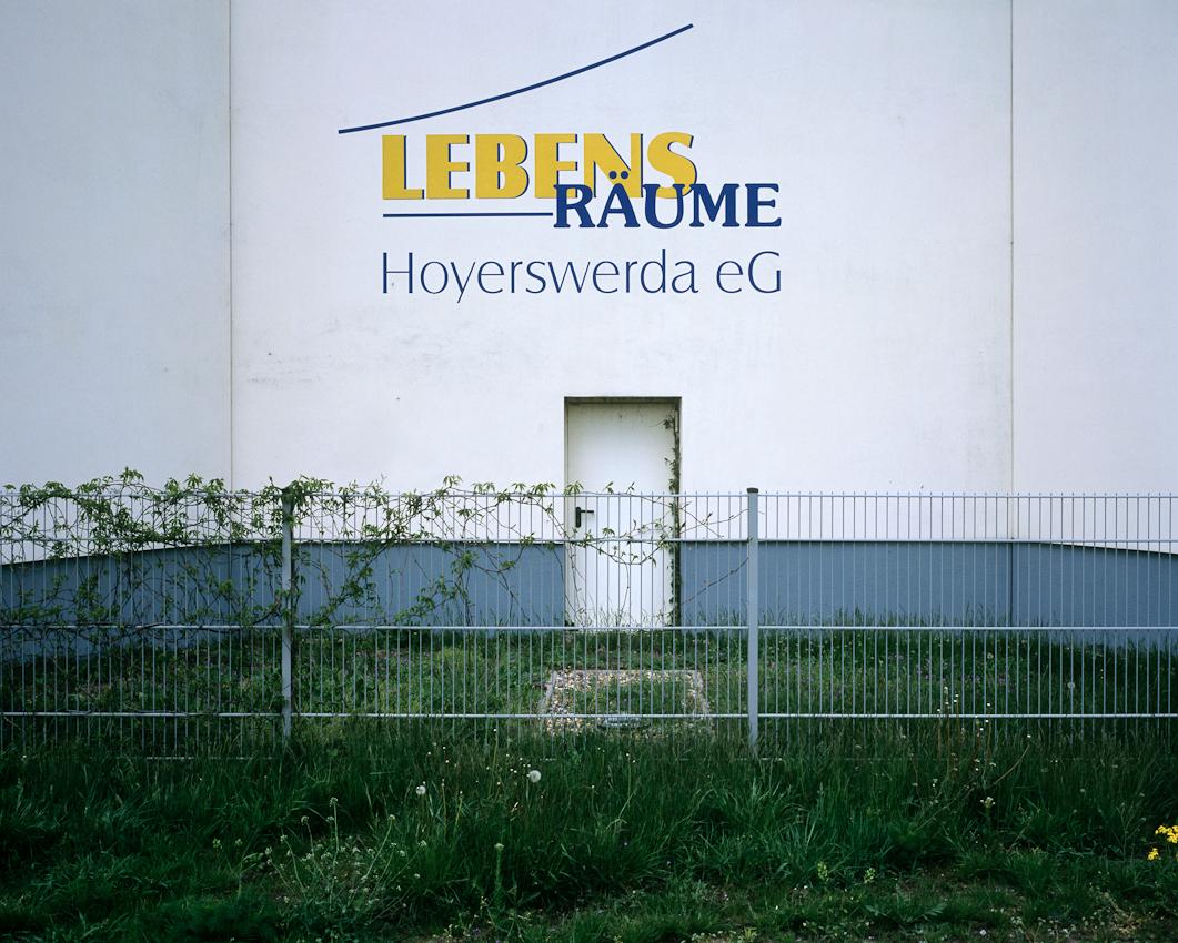 DEU, Deutschland, Germany, Hoyerswerda, Sachsen, 07.05.2010 Logo der Lebensraeume Hoyerswerda eG an einem renovierten Hochhaeus im Plattenbaustil der Lebensraeume eG im Wohnkomplex V in Hoyerswerda-Neustadt. Aus der Serie ' Hoyerswerda - Die Schrumpfende Stadt '. Hoyerswerda-Neustadt mit seinen zehn Wohnkomplexen WK I-X war einst die sozialistische Vorzeigemetropole der DDR. Gekennzeichnet durch die in industrieller Bauweise gefertigten gleichfoermigen Plattenbauten galt es als Modell fuer eine funktionale Stadt der Moderne. Gut Zwanzig Jahre nach dem Mauerfall, ist Hoyerswerda die am staerksten schrumpfende Stadt in Deutschland.
