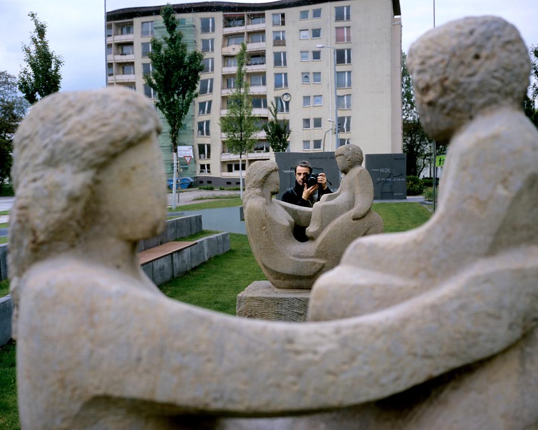 Selbstportrait von Stefan Boness in einer Spiegelung vor dem ersten Plattenbau der DDR in Hoyerswerda-Neustadt. Aus der Serie ' Hoyerswerda - Die Schrumpfende Stadt '. Hoyerswerda-Neustadt mit seinen zehn Wohnkomplexen WK I-X war einst die sozialistische Vorzeigemetropole der DDR. Gekennzeichnet durch die in industrieller Bauweise gefertigten gleichfoermigen Plattenbauten galt es als Modell fuer eine funktionale Stadt der Moderne. Gut Zwanzig Jahre nach dem Mauerfall, ist Hoyerswerda die am staerksten schrumpfende Stadt in Deutschland.