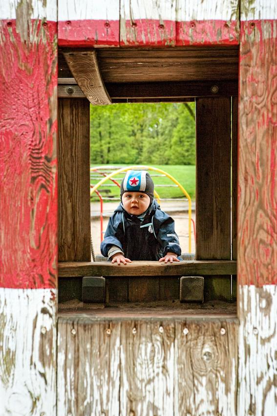 Beobachtung der Erkundung des maritimen Kinderspielplatz im Stadtpark Hamburg/Winterhude durch ein Kleinkind. Das Kleinkind 'Ben' krabbelt durch ein Fenster in einen kleinen Holzleuchtturm. Die Aufnahme wurde am 7.5.2010 um 16:00h gemacht.