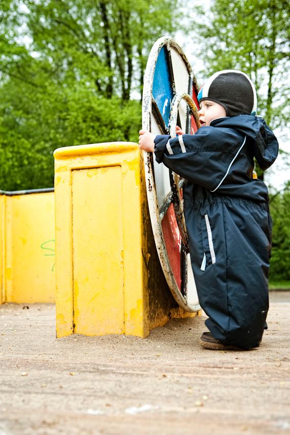 Beobachtung der Erkundung des maritimen Kinderspielplatz im Stadtpark Hamburg/Winterhude durch ein Kleinkind. Das Kleinkind 'Ben' steht am Ruder eines Spielgerüstes in Form eines Bootes. Die Aufnahme wurde am 7.5.2010 um 16:18h gemacht.