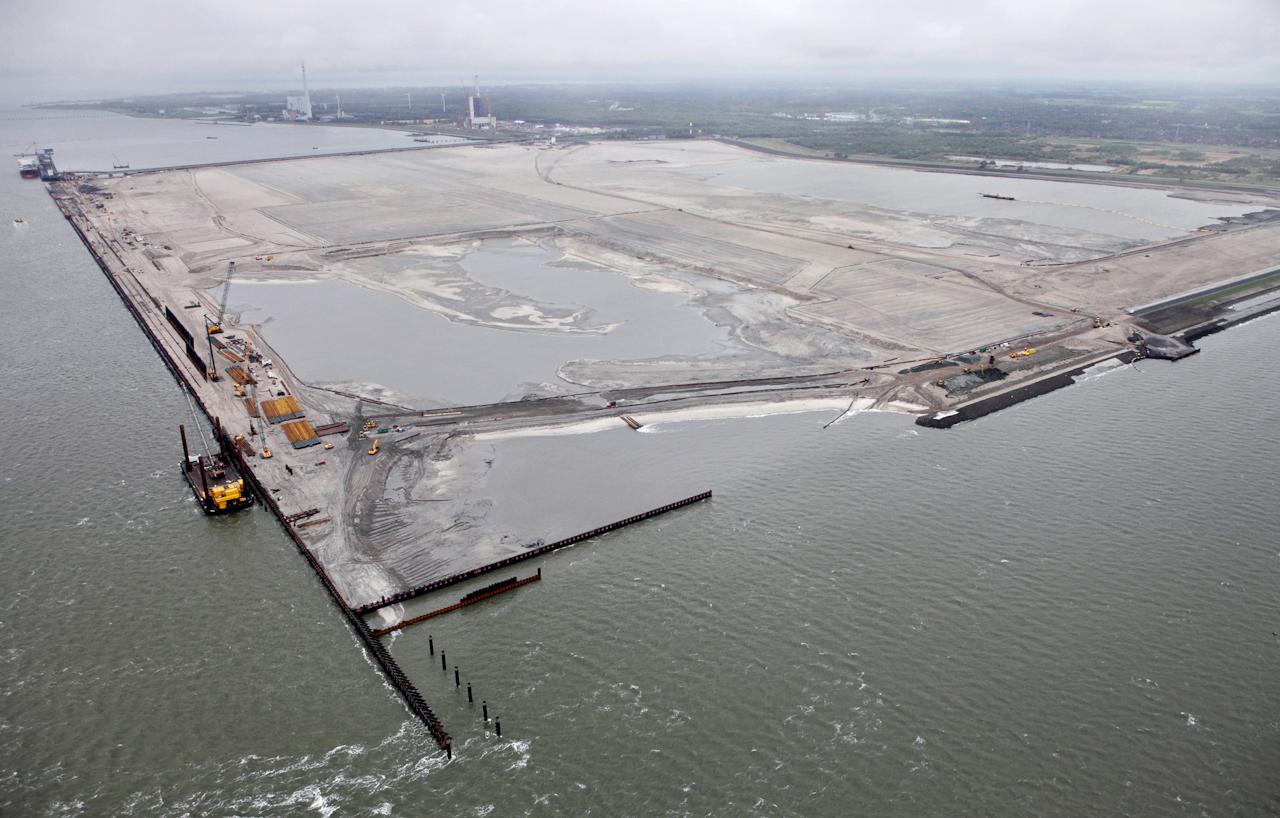 Wilhelmshaven, Niedersachsen, DEU, 07.05.2010, Blick auf die mit Nordseesand aufgespuelte Fläche des JadeWeserPort aus der Luft. In Wilhelmshaven entsteht mit dem JadeWeserPort Deutschlands einziger und von der Tide unabhaengiger Tiefwasserhafen. Mit einer Wassertiefe von 16,5 Meter ist er der einzige Hafen, der kuenftig von den immer groesser werdenden Containerschiffen vollbeladen angelaufen werden kann. Aufgrund des Tiefgangs koennen diese Ozeanriesen Hamburg und Bremerhaven nicht mehr ansteuern - auch nicht nach den geplanten Vertiefungen von Elbe und Aussenweser. In Wilhelmshaven soll vor allem Ladung aus Uebersee fuer den Weitertransport in die Ostsee umschlagen werden. Fuer die Herstellung der 360 Hektar grossen Hafenflaeche werden ueber 40 Millionen Kubikmeter Sand benoetigt. Saugbagger entnehmen der Nordsee das Sand-Wasser-Gemisch und transportieren es durch ein schwimmendes Rohrleitungsnetz bis auf das Spuelfeld. Das Wasser laeuft zurueck in die Nordsee, der Sand bleibt liegen und bildet das Neuland. 2011 sollen die ersten 1.000 Metern Kaje (Kai) eroeffnet werden - 2012 geht der gesamte Hafen in Betrieb. Weitere Infos unter www.jade-weser-port.de