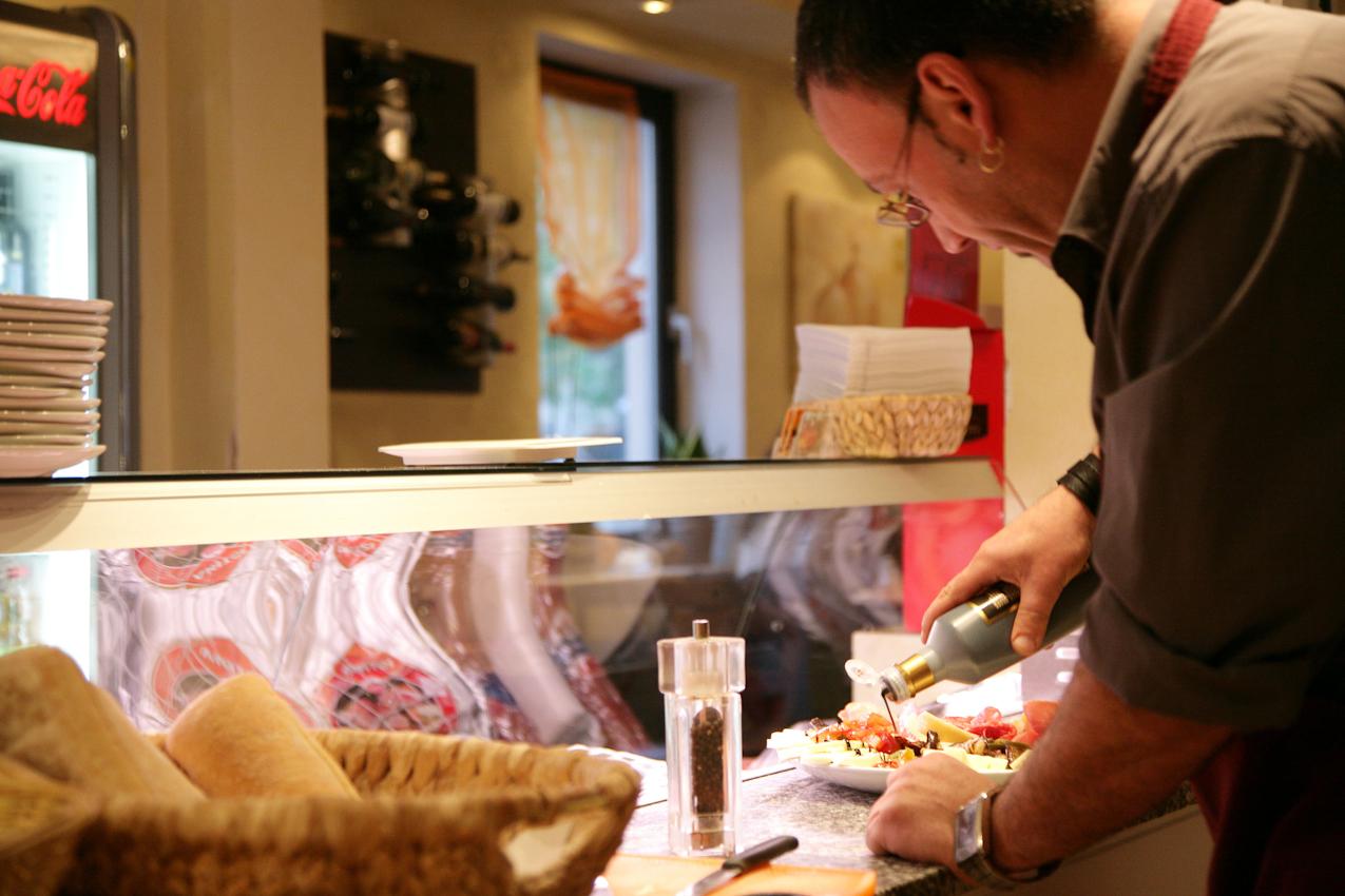Restaurant Buongiorno Italia (Ciabatteria, Enoteca und Eis-Cafe) in Erlangen, Obere Karlstrasse 34, Kellner Antonio bei der Zubereitung einer Antipastiplatte indem er zum zum Abschluss der Zubereitung etwas Balsamico Essig uber die Zutaten verteilt.