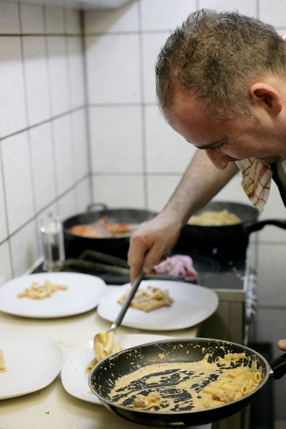 Restaurant Buongiorno Italia (Ciabatteria, Enoteca und Eis-Cafe) in Erlangen, Obere Karlstrasse 34, Fernando Particolare (Ehemann der Inhaberinn Maria Rosaria Particolare und Koch) beim Verteilen einer Nudelspeise auf Teller in der Küche des Restaurants.