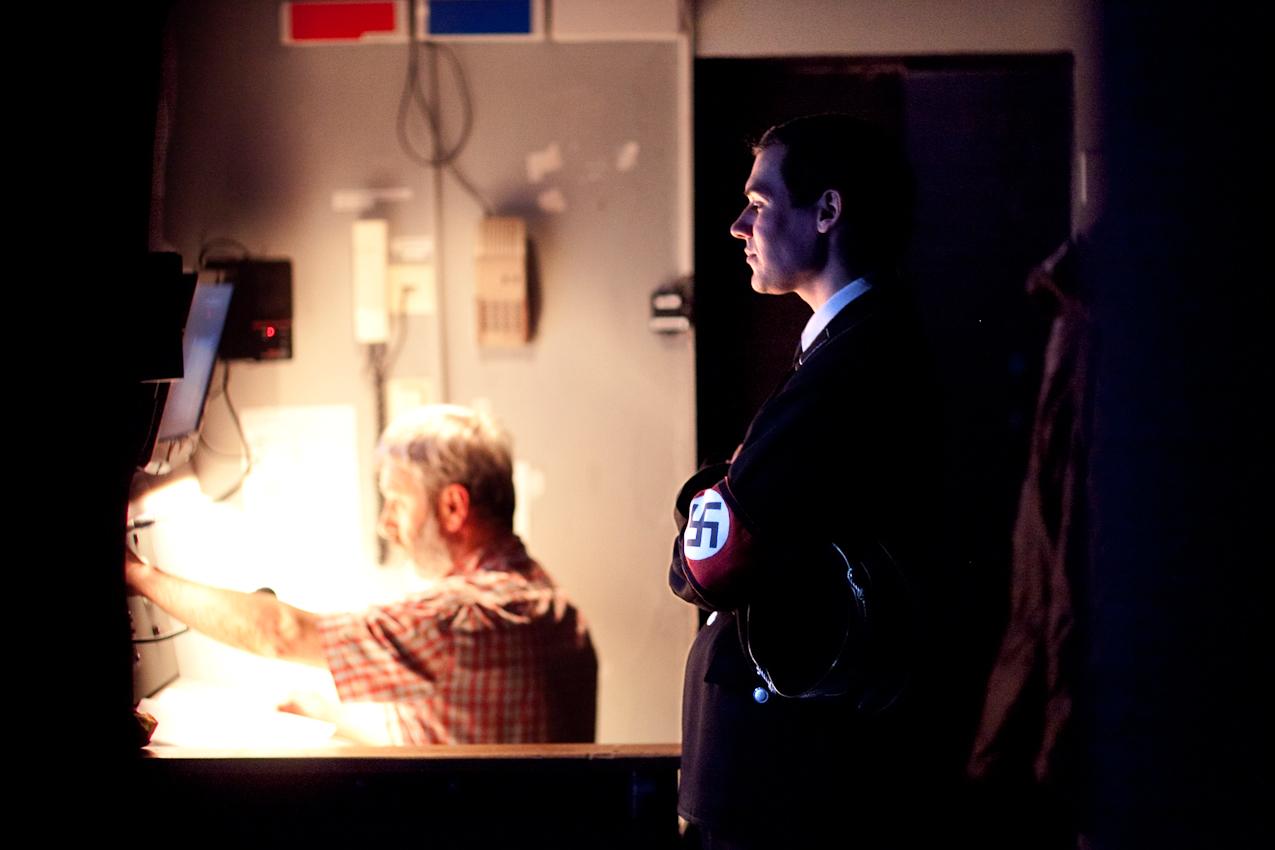 """Abendvorstellung von """" Sein oder Nichtsein """" nach dem Film von Ernst Lubitsch am Staatsschauspiel Dresden, grosse Buehne. Backstage fotografiert von der Nebenbuehne aus. Freitag, 7. Mai 2010, 20.26 Uhr.  Der Schauspieler Marcus Horn, der einen SS Mann spielt, verfolgt das Buehnengeschehen auf den Monitoren von Inspizient Detlef Mueller."""
