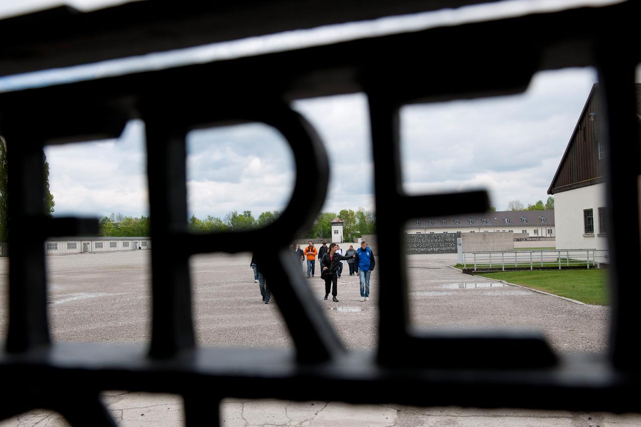 """Am 2. Mai 1945 wurde das KZ Dachau von amerikanischen Truppen befreit. Der Förderverein fur internationale Jugendbegegnung und Gedenkstättenarbeit e.V. organisiert jedes Jahr den Besuch ehemaliger KZ-Häftlinge in Dachau.  Blick durch den Schriftzug """"Arbeit macht frei""""."""