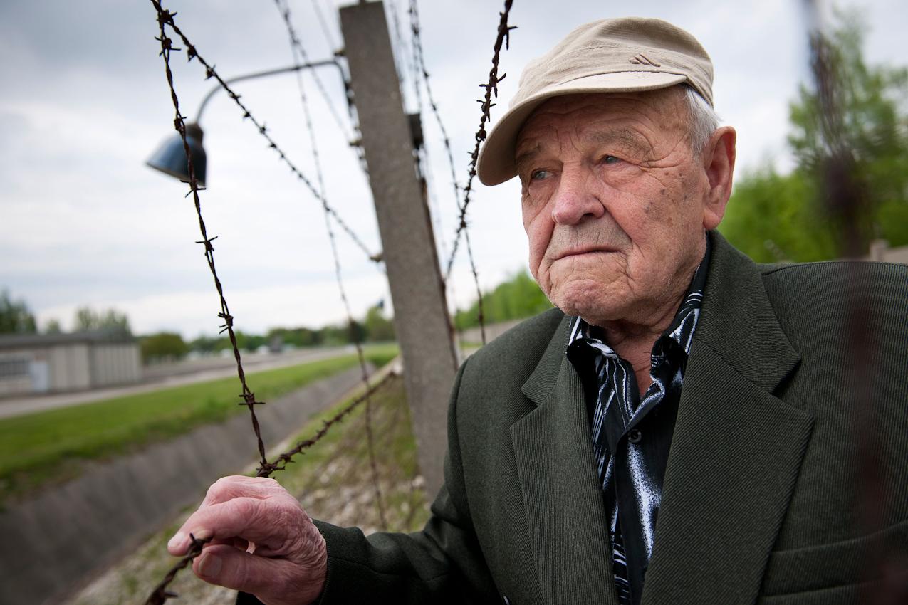 Am 2. Mai 1945 wurde das KZ Dachau von amerikanischen Truppen befreit. Der Förderverein fur internationale Jugendbegegnung und Gedenkstättenarbeit e.V. organisiert jedes Jahr den Besuch ehemaliger KZ-Häftlinge in Dachau.  Nikolaj Gorbenko (87) aus der Ukraine am Stacheldraht des Todesstreifens. Obwohl er nur in Außenlagern untergebracht war, hört er die Stimmen von damals auf dem Appellplatz.