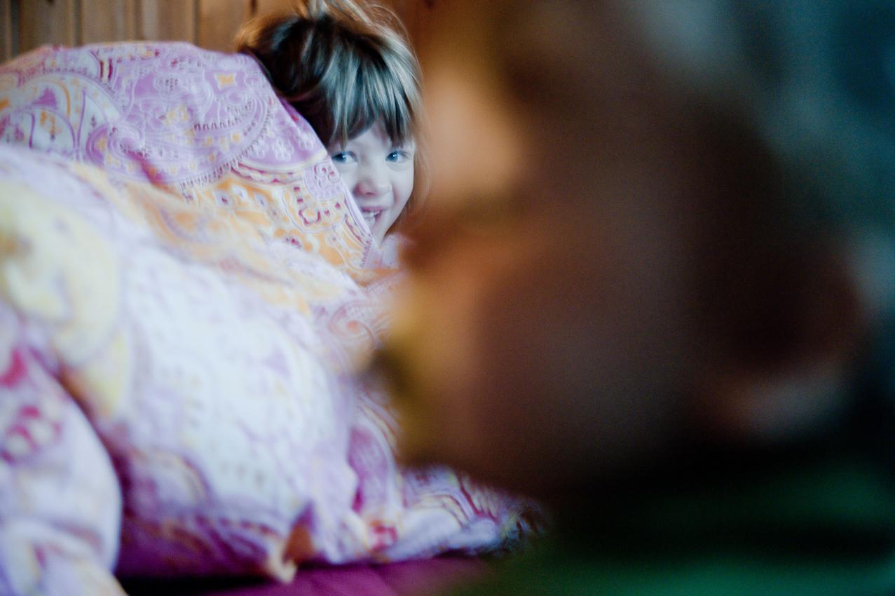 """7.17 Uhr, Schlafzimmer: Nia ist in der Nacht wach geworden und hat anschließend im Bett von Mama und Papa schlafen dürfen. Sie ist vom Gequengel ihres kleinen Bruders aufgewacht. Im Vordergrund (unscharf) steht der Bruder Levin am Bett. Das Foto wurde am 07.05.2010 für das Projekt """"Ein Tag Deutschland"""" aufgenommen im Rahmen einer Fotoserie über das Alltagsleben einer Kleinfamilie im Dorf Maintal-Wachenbuchen, 15 Km östlich von Frankfurt am Main. Bei der Serie geht es darum den normalen Alltag eine Kleinfamilie zu zeigen, bei der nach klassischem Rollenmodell vorwiegend die Mutter für die Erziehung der Kinder zuständig ist. Die Mutter arbeitet freiberuflich als Fotografin, der Vater geht einem klassischen Bürojob nach und arbeitet jeden Tag 20 km entfernt. Miteinander, Nebeneinander und Gegeneinander sind das Thema der Serie mit Fokus auf der Beziehung der Geschwister untereinander, die den Familienalltag maßgeblich mitbestimmen. Die Serie über den Familienalltag ist als Langzeitprojekt angelegt. Die Fotos entstanden alle in der Wohnung der Familie, die Dreh- und Angelpunkt des Familienlebens ist. Zur Familie gehören der Vater Thomas Schäfer, die Mutter Meike Fischer (die auch fotografiert hat), die 5-jahrige Tochter Nia und der 14 Monate alte Sohn Levin."""