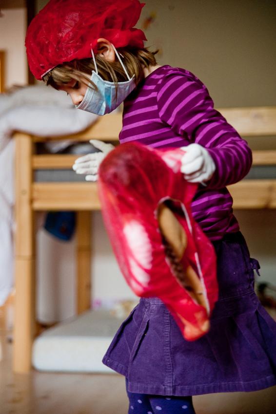 """14.31 Uhr, Kinderzimmer: Nach dem Kindergarten spielt Nia mit ihrem Arztkoffer Krankenhaus und verarztet ihre Puppe, nachdem sie schon ihren Bruder untersucht hat. An manchen Tagen verabredet sich Nia nicht mit Freundinnen und ist dann am Nachmittag zuhause mit ihrer Mutter und dem kleinen Bruder.  Das Foto wurde am 07.05.2010 für das Projekt """"Ein Tag Deutschland"""" aufgenommen im Rahmen einer Fotoserie über das Alltagsleben einer Kleinfamilie im Dorf Maintal-Wachenbuchen, 15 Km östlich von Frankfurt am Main. Bei der Serie geht es darum den normalen Alltag eine Kleinfamilie zu zeigen, bei der nach klassischem Rollenmodell vorwiegend die Mutter für die Erziehung der Kinder zuständig ist. Die Mutter arbeitet freiberuflich als Fotografin, der Vater geht einem klassischen Bürojob nach und arbeitet jeden Tag 20 km entfernt. Miteinander, Nebeneinander und Gegeneinander sind das Thema der Serie mit Fokus auf der Beziehung der Geschwister untereinander, die den Familienalltag maßgeblich mitbestimmen. Die Serie über den Familienalltag ist als Langzeitprojekt angelegt. Die Fotos entstanden alle in der Wohnung der Familie, die Dreh- und Angelpunkt des Familienlebens ist. Zur Familie gehören der Vater Thomas Schäfer, die Mutter Meike Fischer (die auch fotografiert hat), die 5-jahrige Tochter Nia und der 14 Monate alte Sohn Levin."""