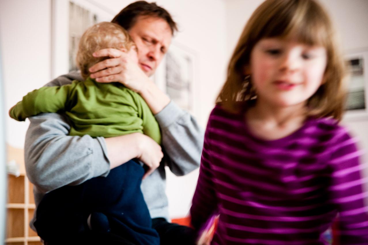 """17.36 Uhr, Wohnzimmer: Nachdem er im Streit von Nia gezwickt wurde, wird Levin von seinem Papa Thomas getröstet. Häufig ist sie eifersüchtig auf den Bruder, der sehr viel Aufmerksamkeit von den Eltern fordert. Nia rennt derweil in ihr Zimmer, weil sie nicht mochte, dass mit ihr geschimpft wird.  Das Foto wurde am 07.05.2010 für das Projekt """"Ein Tag Deutschland"""" aufgenommen im Rahmen einer Fotoserie über das Alltagsleben einer Kleinfamilie im Dorf Maintal-Wachenbuchen, 15 Km östlich von Frankfurt am Main. Bei der Serie geht es darum den normalen Alltag eine Kleinfamilie zu zeigen, bei der nach klassischem Rollenmodell vorwiegend die Mutter für die Erziehung der Kinder zuständig ist. Die Mutter arbeitet freiberuflich als Fotografin, der Vater geht einem klassischen Bürojob nach und arbeitet jeden Tag 20 km entfernt. Miteinander, Nebeneinander und Gegeneinander sind das Thema der Serie mit Fokus auf der Beziehung der Geschwister untereinander, die den Familienalltag maßgeblich mitbestimmen. Die Serie über den Familienalltag ist als Langzeitprojekt angelegt. Die Fotos entstanden alle in der Wohnung der Familie, die Dreh- und Angelpunkt des Familienlebens ist. Zur Familie gehören der Vater Thomas Schäfer, die Mutter Meike Fischer (die auch fotografiert hat), die 5-jahrige Tochter Nia und der 14 Monate alte Sohn Levin."""