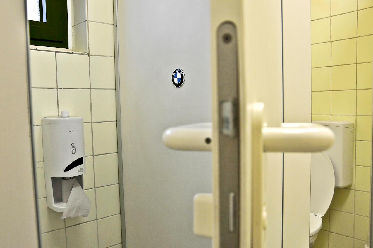 An der Beladestelle in Berlin-Reinickendorf am 07.05.2010 um 07:07 Uhr: Männerklo mit dem BMW-Logo in Augenhohe beim Sitzen auf der Toilette.