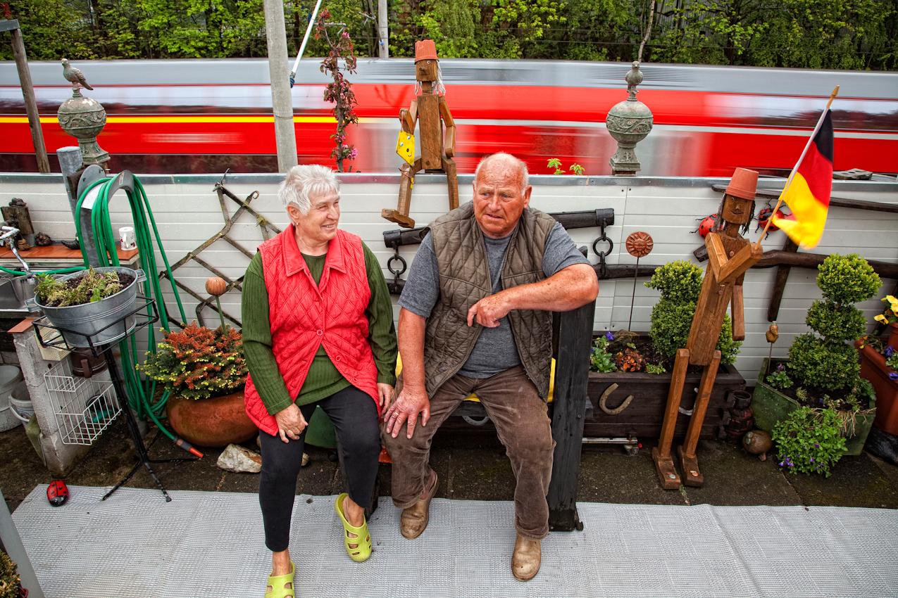 Das Ehepaar Gisela (74) und Uwe Pfadler (70) hat den Garten in Ordnung gebracht und ruht sich auf der Bank am Bahndamm der Strecke Hamburg - Lübeck aus.