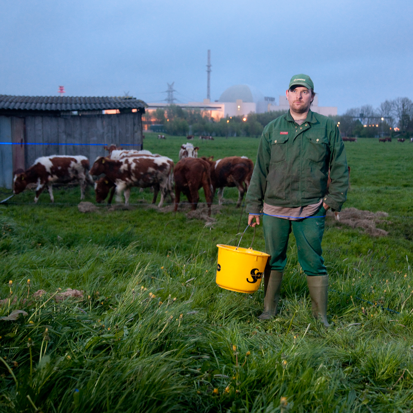 """Ilse Mross und ihr Sohn Carsten bewirtschaften ihren Bauernhof direkt neben dem Kernkraftwerk Brokdorf an der Elbe. Am Ende des Tages bekommen die Kälber noch einmal Futter, dann ist Feierabend. Die blaue Linie simuliert den gestiegenen Meerespiegel am Ende des Jahrhundert, wie er von Klimaexperten wegen des Klimawandels vorhergesagt wird. Das Bild ist Teil einer Serie """"Waterlines"""" die sich mit den Folgen eines weltweiten Meeresspiegelanstiegs beschäftigt."""