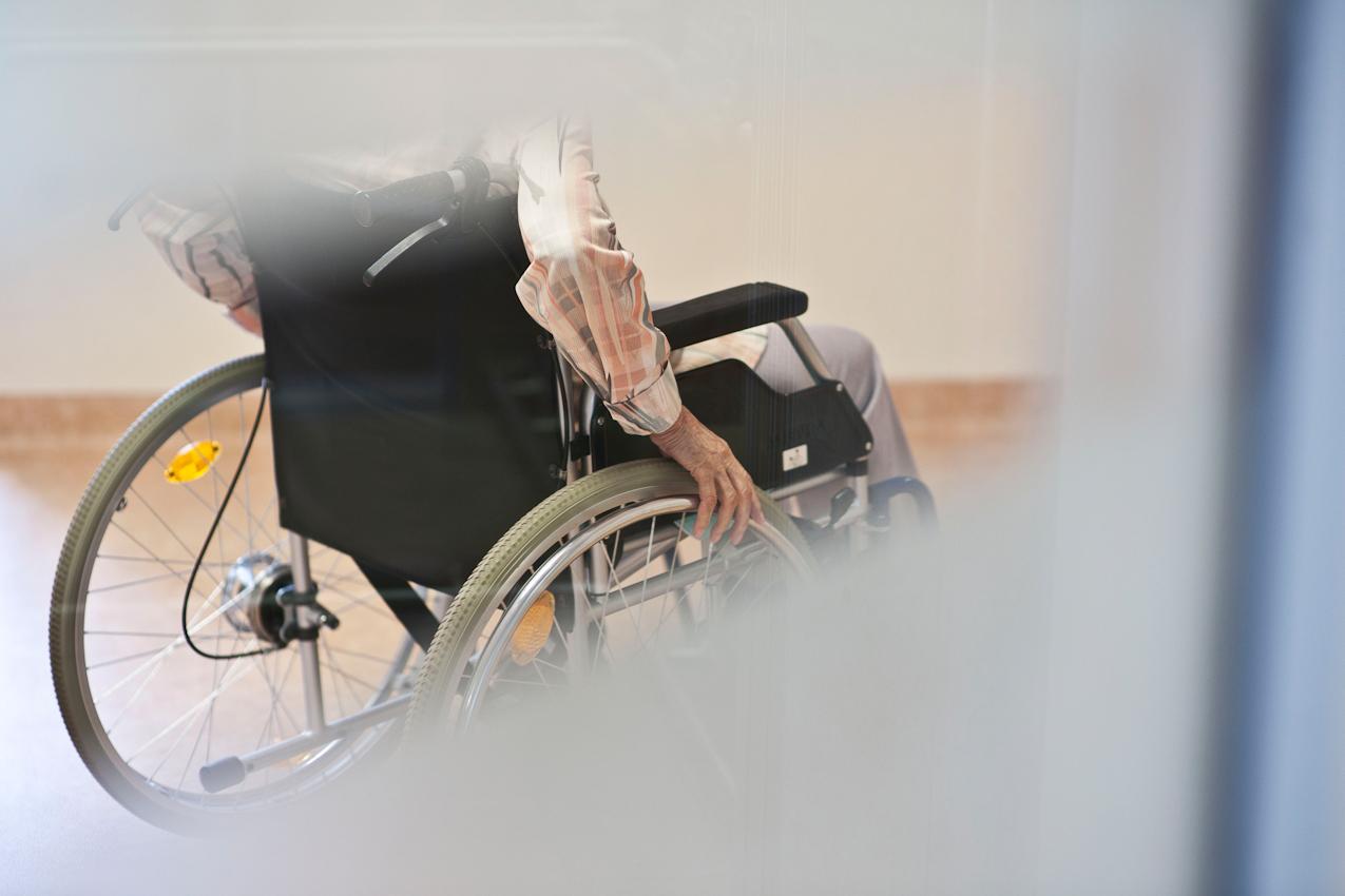 Ein Bewohner im Rollstuhl faehrt uber den Flur der Pflegestation. Weil immer mehr hochgradig verwirrte Menschen mit Fluchttendenz in den Altenheimen leben, sind die Ausgaenge haeufig mit speziellen Vorrichtungen gesichert, die die Eingabe eines Zahlencodes oder das Druecken einer Taste erfordern. Das Bild ist entstanden im Parkstift St. Ulrich des Kuratoriums Wohnen im Alter in Bad Duerrheim am 7.5.2010.