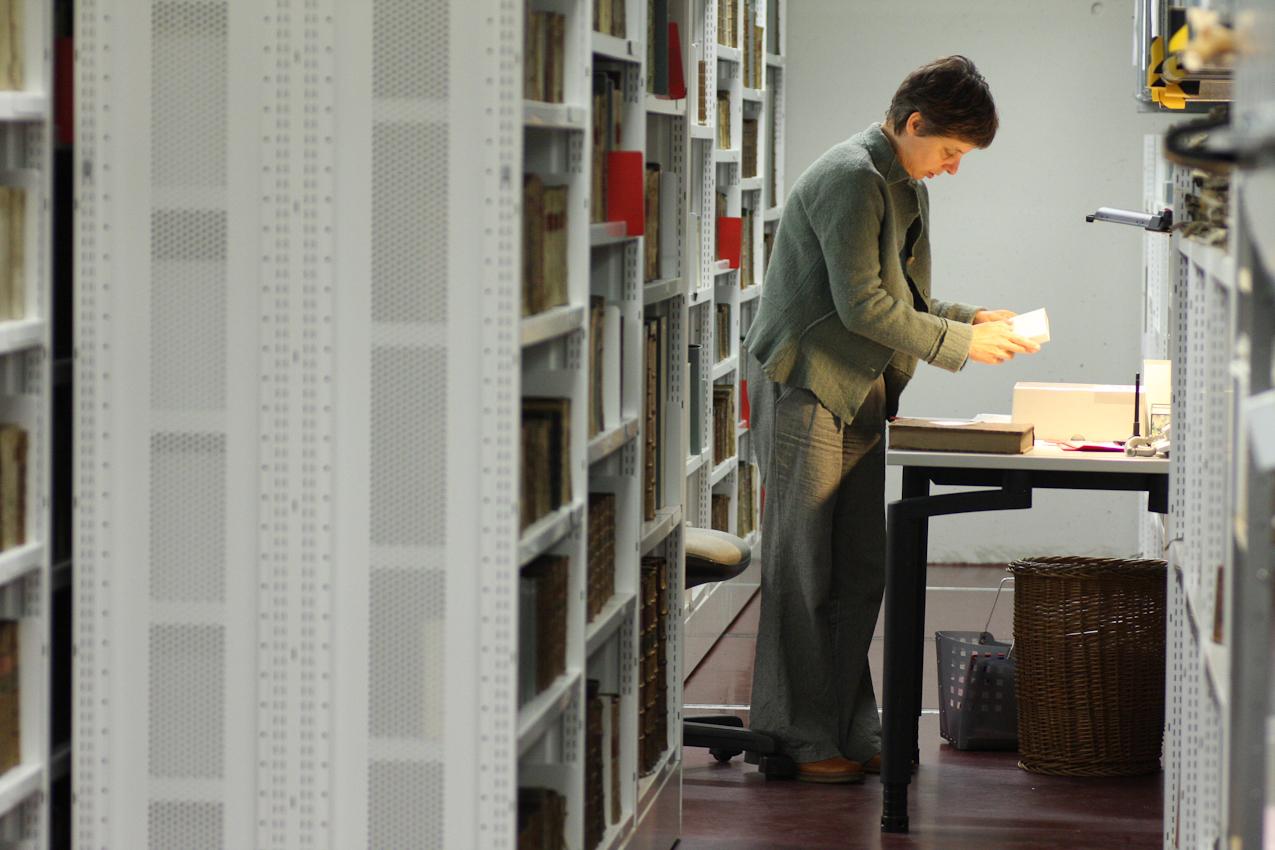 Susanne Kaerner, Betreuerin der Buchbinderei der Universitätsbibliothek Mannheim. Die Werkstatt ist zuständig sowohl für das Buchbinden (meisten sind neue Bücher) als auch für Konservierung und Reparieren der alten Bücher, die vor 1850 erschien sind. Gerade ist Susanne Kaerner in der Tiefmagazine der Universitätsbibliothek Mannheim, wo die alten Bücher unter besonderen Bedingungen (Temperatur, Feuchtigkeit etc.) aufbewahrt werden. Sie bringt die Bucher nach der Reparatur zurück. Das Foto wurde um 11:47 aufgenommen.