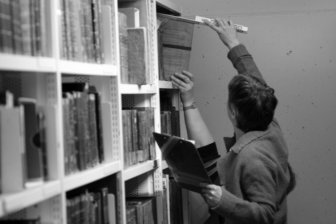 Susanne Kaerner, Betreuerin der Buchbinderei der Universitätsbibliothek Mannheim. Die Werkstatt ist zuständig sowohl für das Buchbinden (meisten sind neue Bücher) als auch für Konservierung und Reparieren der alten Bücher, die vor 1850 erschien sind.  Gerade ist Susanne Kaerner in der Tiefmagazine der Universitätsbibliothek Mannheim, wo die alten Bucher unter besonderen Bedingungen (Temperatur, Feuchtigkeit etc.) bewahren werden. Sie misst die Bücher, um Verpackungen für sie zu bestellen. Das Foto wurde um 12:20 aufgenommen.