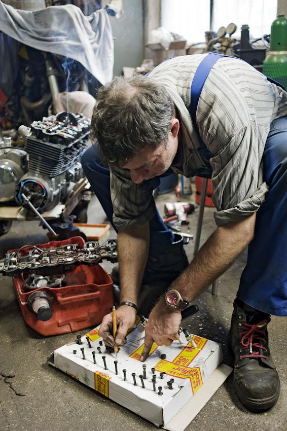 Peter Pulkow hat den Kopf des 6-Zylinder-Motors einer Benelli, eines Italienischen Motorrades, abgeschraubt und beschriftet jetzt die verschiedenen Schrauben des Nockenwellenlagers und der Kopfdichtung fuer den spaeteren Zusammenbau. Pulkow betreibt seine KFZ-Meisterwerkstatt fuer alle Arten und Typen in einem schmalen Hinterhof in der Chausseestrasse Berlin-Mitte.
