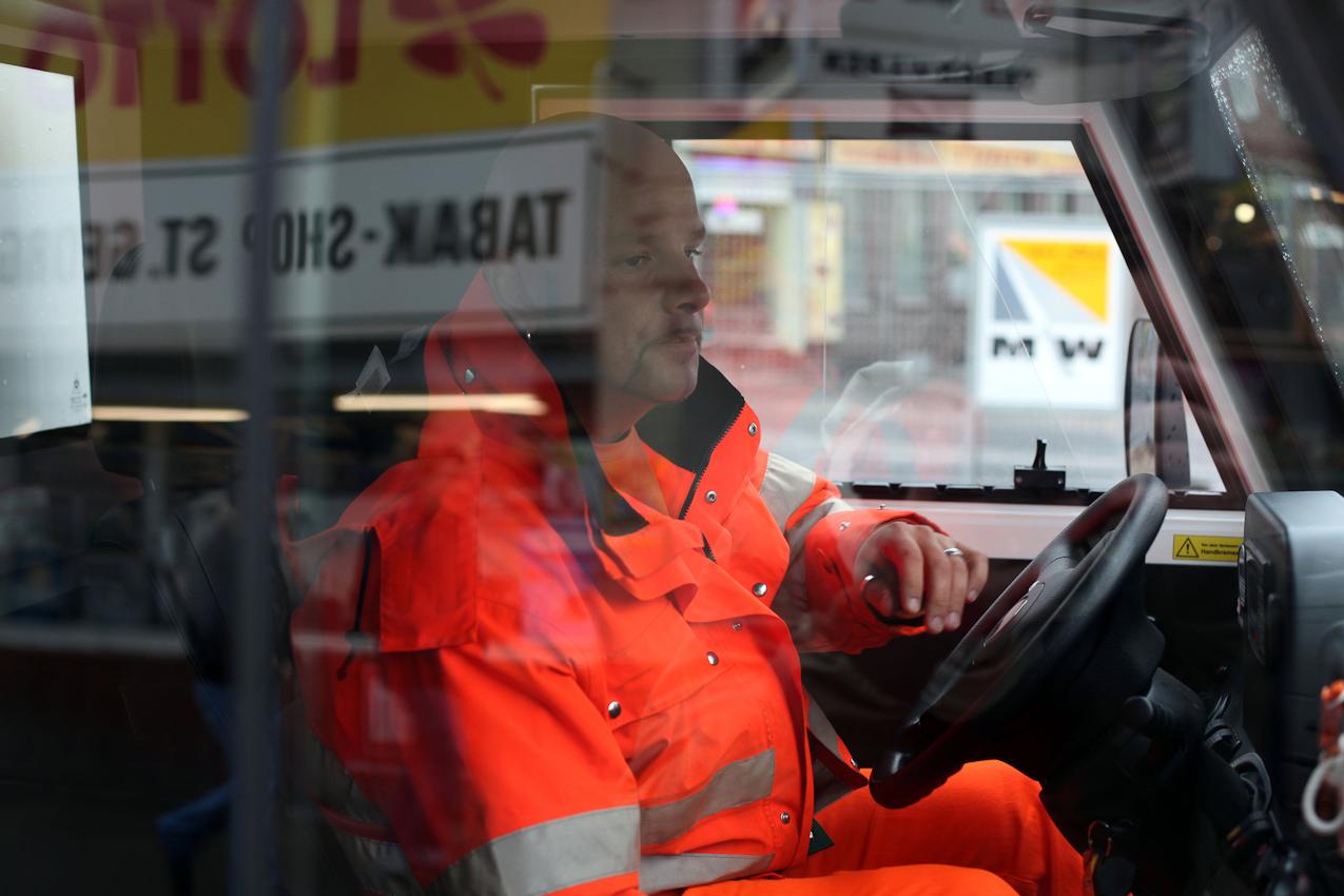 Robert Szwejk sitzt am Steuer des Elektromobils. Er ist Mitarbeiter der Stadtreinigung Hamburg und zuständig für den Hansaplatz und einige der umliegenden Straßen. Seine Aufgabe ist es, die Mülleimer zu leeren und dafür zu sorgen, dass Wege und Straßen sauber bleiben.