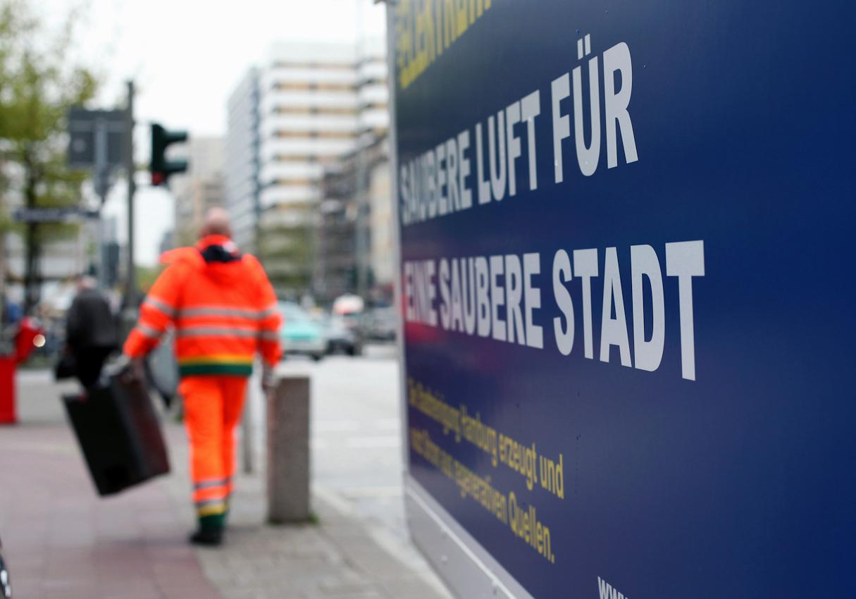 Robert Szwejk mit gerade geleertem Mülleimer in der Hand von hinten. An der rechten Bildseite ist die Aufschrift des Elektromobils der Stadtreinigung Hamburg zu sehen.