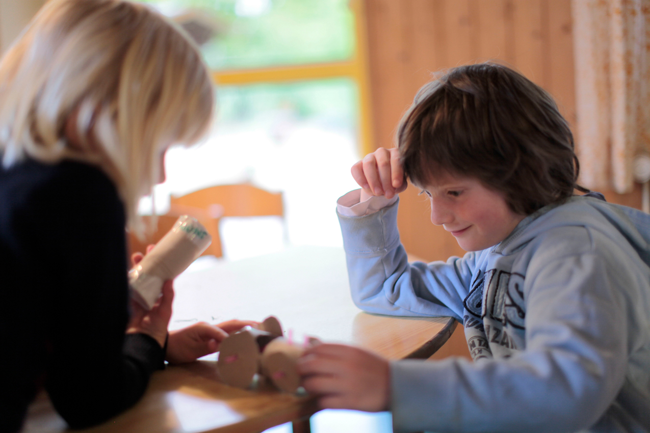 Adina (5) und Luca (5) begutachten Lucas' aus Klorollen, Pappe und Strohhalmen selbstgebastelten Traktor, Adina hält eine aus Klorollen gebastelte Rassel in der Hand.