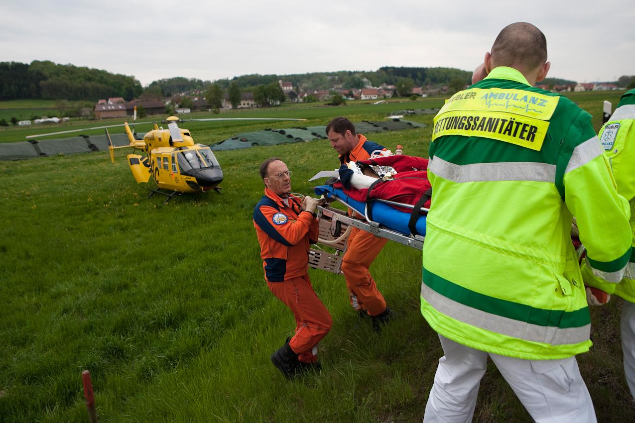 Dr. M. Helm, der Pilot Christian Stangl und die Rettungssanitäter tragen den Verletzten vom Unfallort zum Hubschrauber.