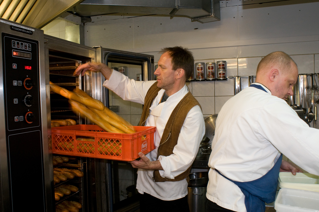 """Der Küchenchef Martin Tausendfreund (r.) und der Souschef Rechou Maurer (l.) bereiten sich auf das demnächst beginnende Abendgeschäft vor. Auch das Brot wird täglich in der Küche des """"TIPI"""" frisch gebacken."""