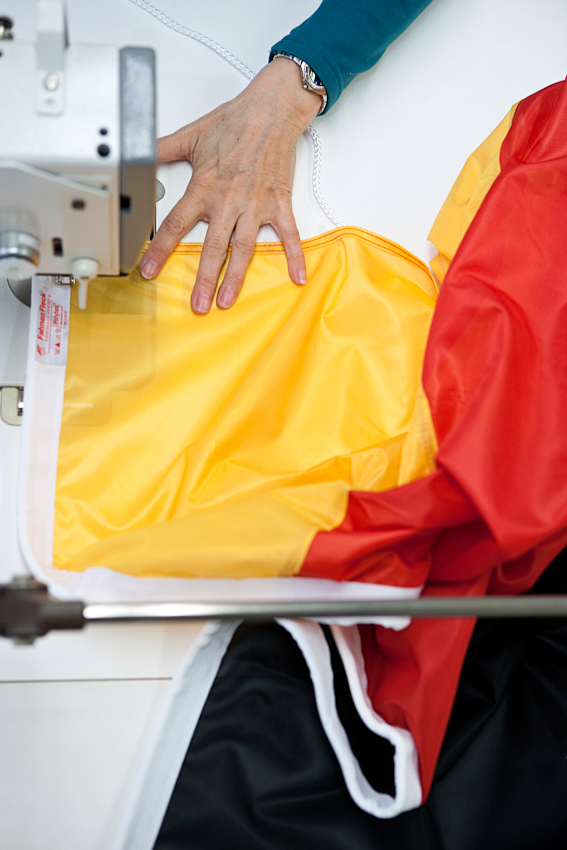 Eine Näherin beim Säumen einer Deutschlandfahne.
