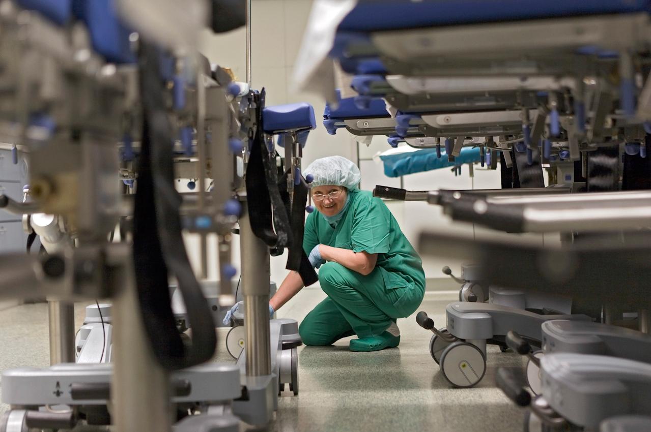 Prof. Dr. med. Thomas Hupp operiert Waldemar Goetz im Klinikum Stuttgart, OP-Saal 4 an der Halsschlagader. Putzfrau Valentina Mironov putzt morgens die OP-Liegen vor deren Einsatz.