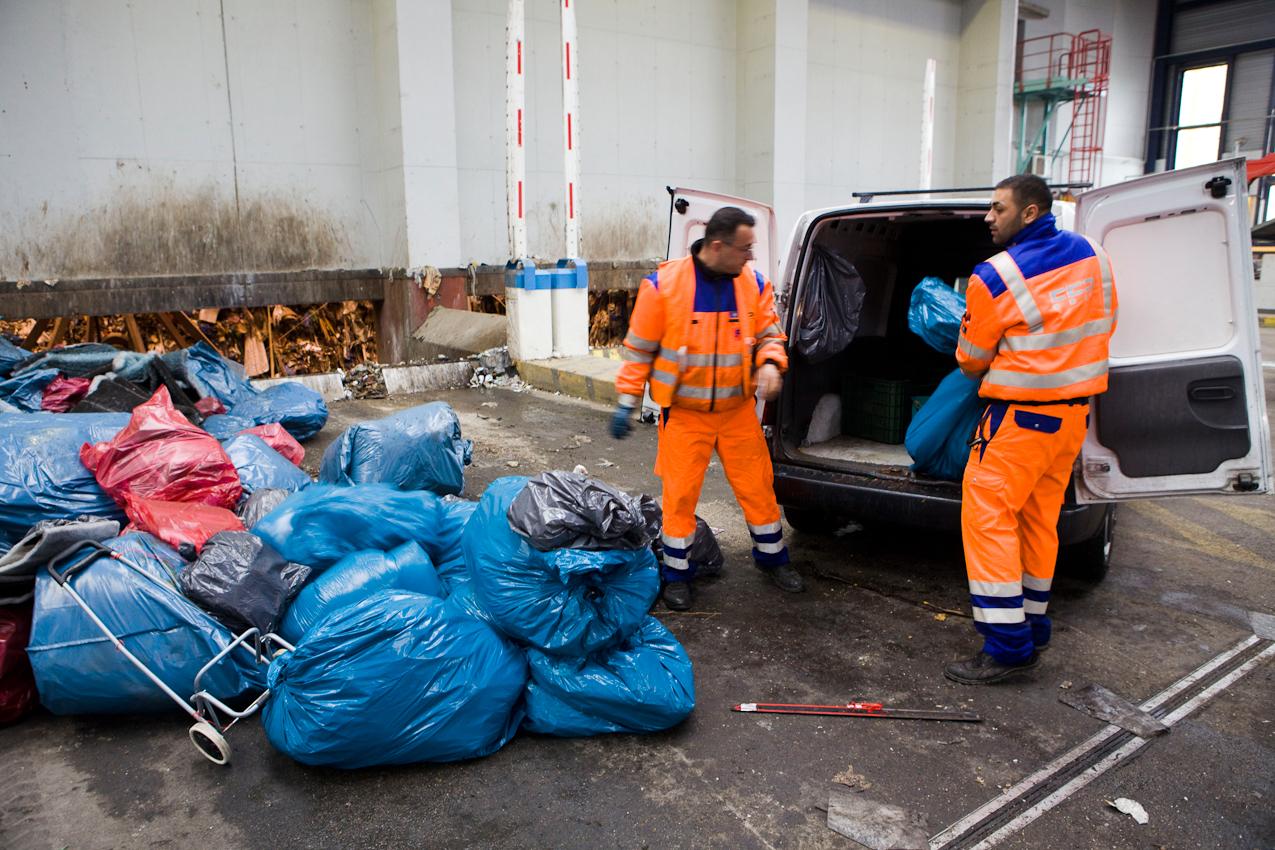 Vor dem Zugang zu einer Schleuse in den Müllbunker laden die zwei FES-Mitarbeiter Mehmet Kilinc und Ismet Arsoy (v.l.n.r.) Müll ab.