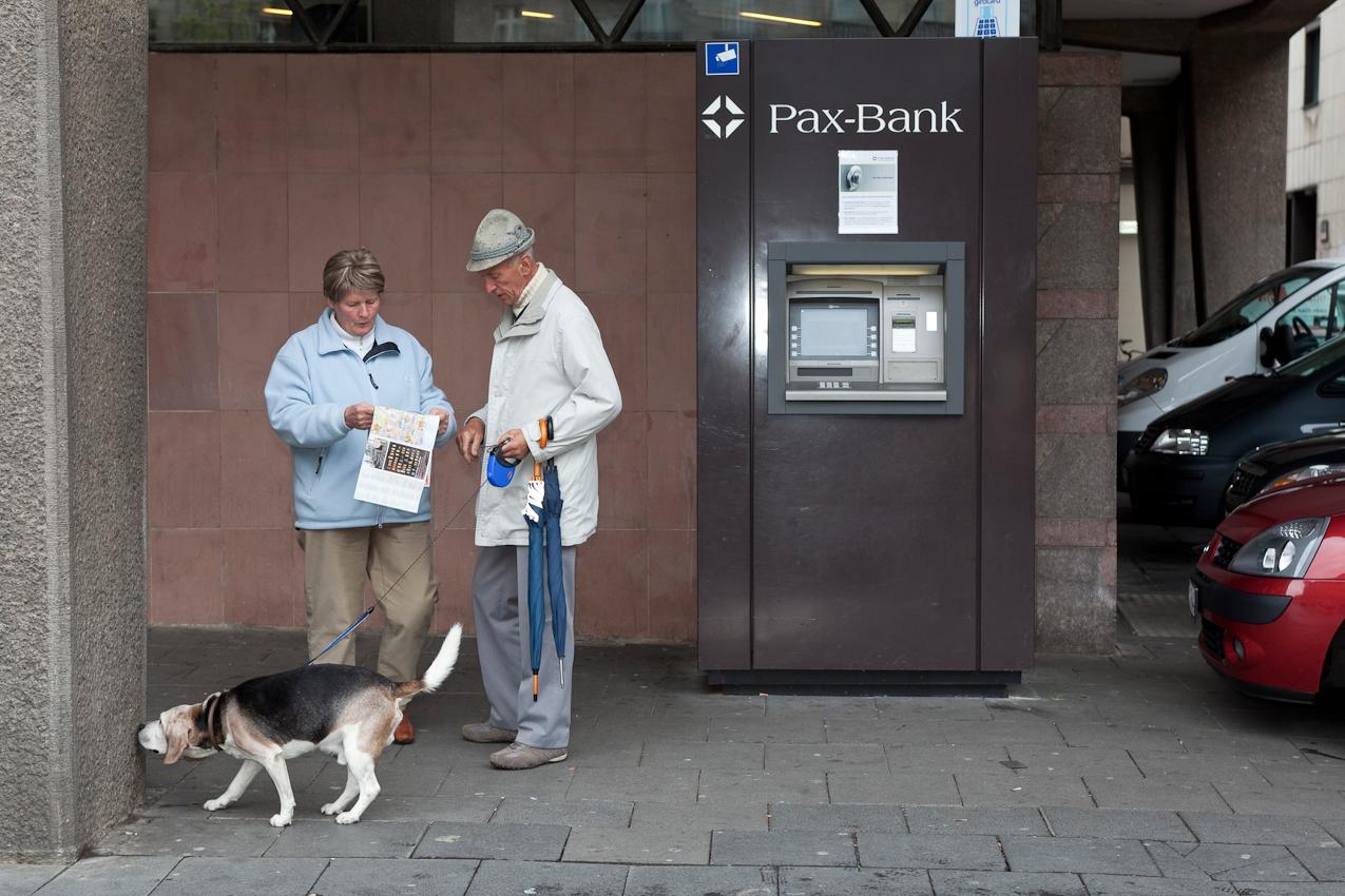 Ein Touristen-Ehepaar mit Stadtplan und Hund vor einem Geldautomaten am Domforum.