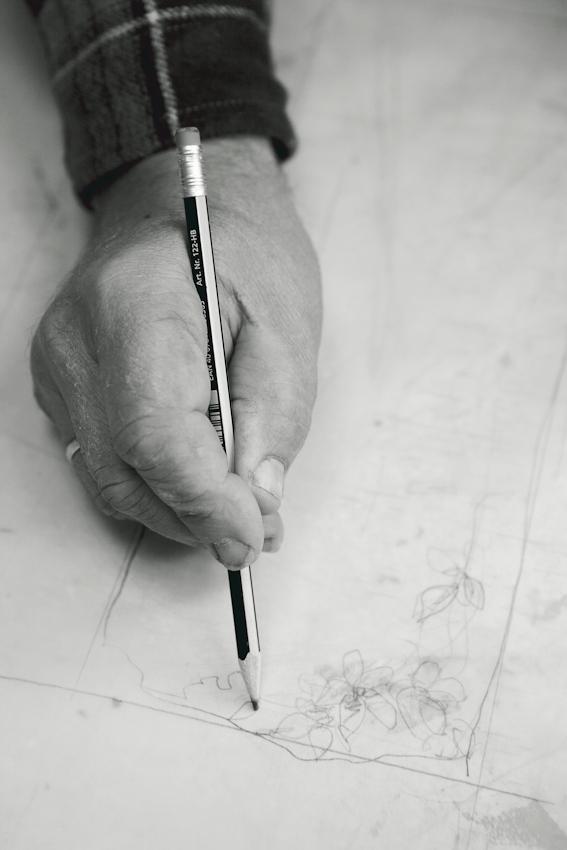 Die Hand vom Steinmetz Stefan Behrends in seinem Steinmetzbetrieb in Hamburg-Volksdorf. Er zeichnet Entwürfe für den Auftrag eines Grabmals, auf dem später eine Clematis zu sehen sein soll.