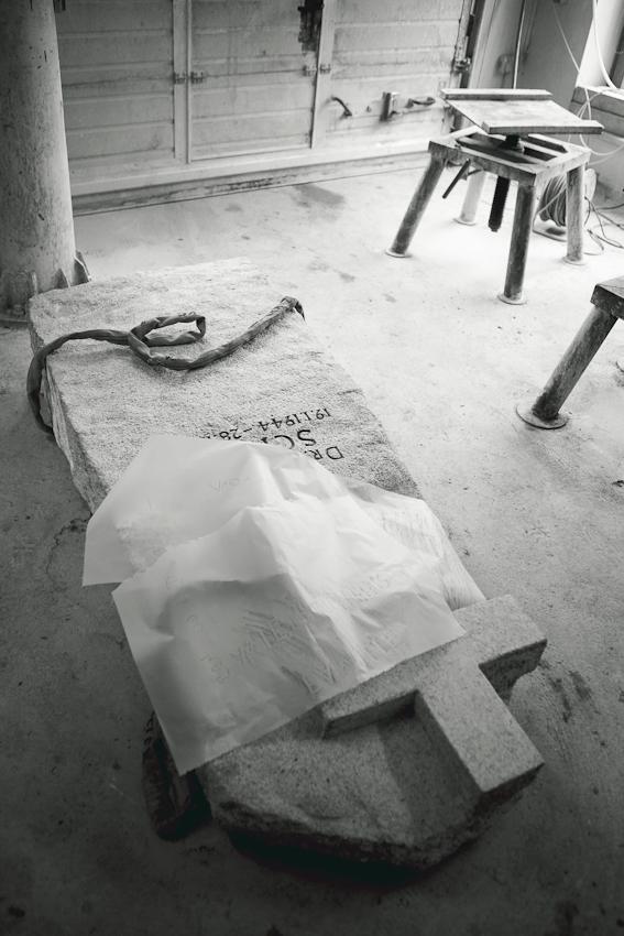 """Die Werkstatt von """"Schwabs Steinmetzbetrieb"""" in Hamburg Volksdorf. Auf dem Boden liegt ein Grabmal, an dem gerade gearbeitet wird."""