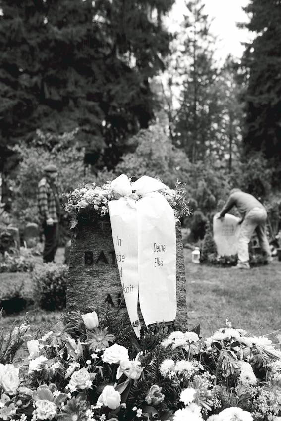 Steinmetz Stefan Behrends und sein ehemaliger Geselle, der Steinmetz Rüdiger Eckert beim Aufstellen und Befestigen eines Grabmals auf dem Friedhof in Hamburg-Volksdorf.