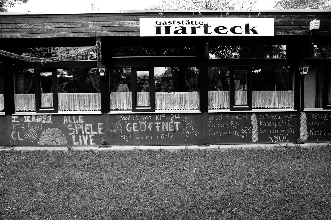 Die Gaststätte Harteck am Eingang zur Kleingartenanlage mit Aufschriften aus Kreide, um auf die nächsten Fußballspiele hinzuweisen, die man hier gemeinsam anschauen kann und die Speisekarte mit besonders für München äußerst günstigen Preisen.