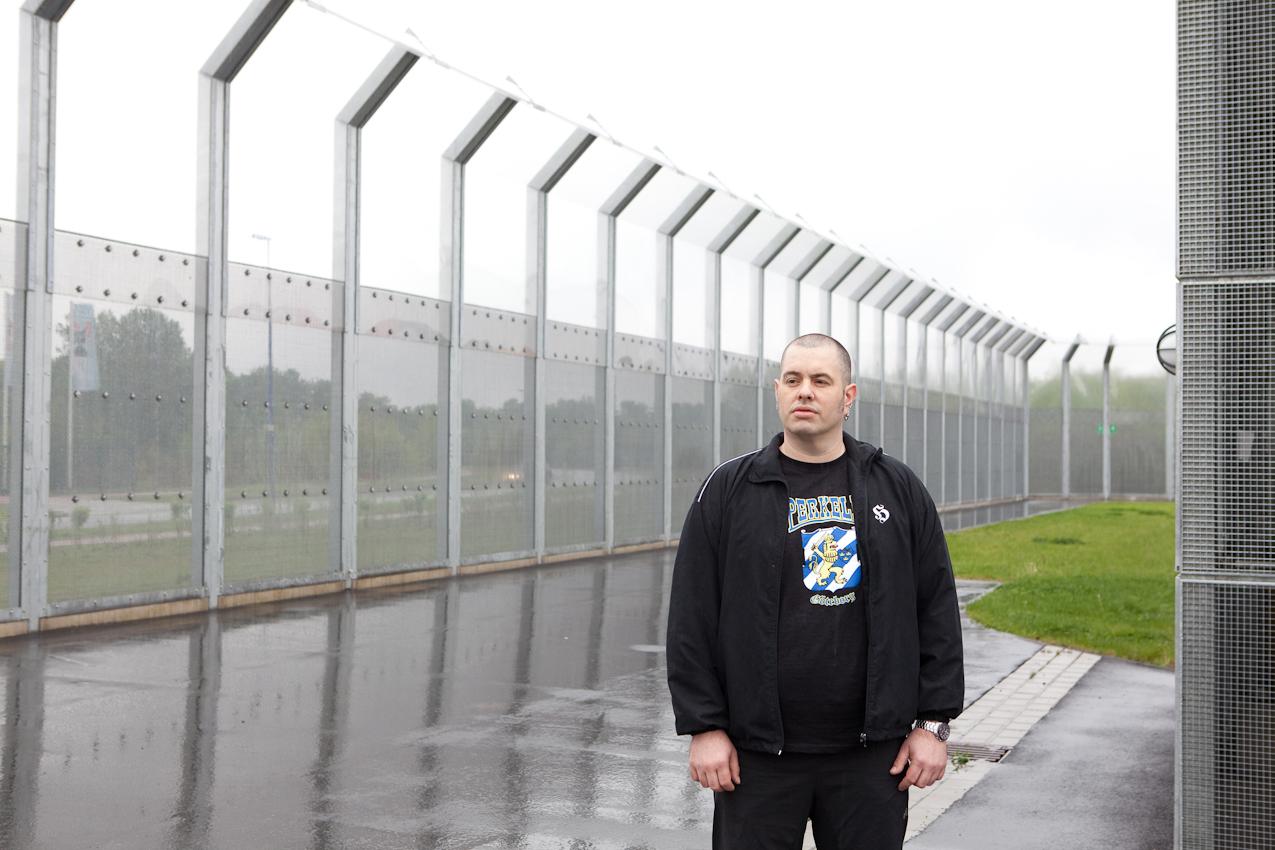 Die Aufnahme zeigt Christian M. am Zaun der Klinik, der Grenze zwischen dem überwachten Gelände und der Freiheit.