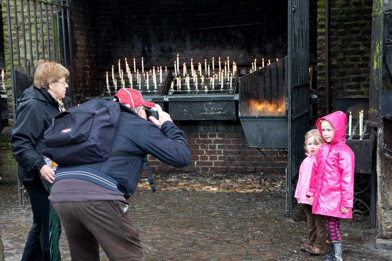 Ein niederländisches Rentnerehepaar (Wallfahrer) fotografiert seine Enkelkinder auf dem Kapellenplatz an der Kerzenkapelle. Im Hintergrund sind Opferkerzen zu sehen.
