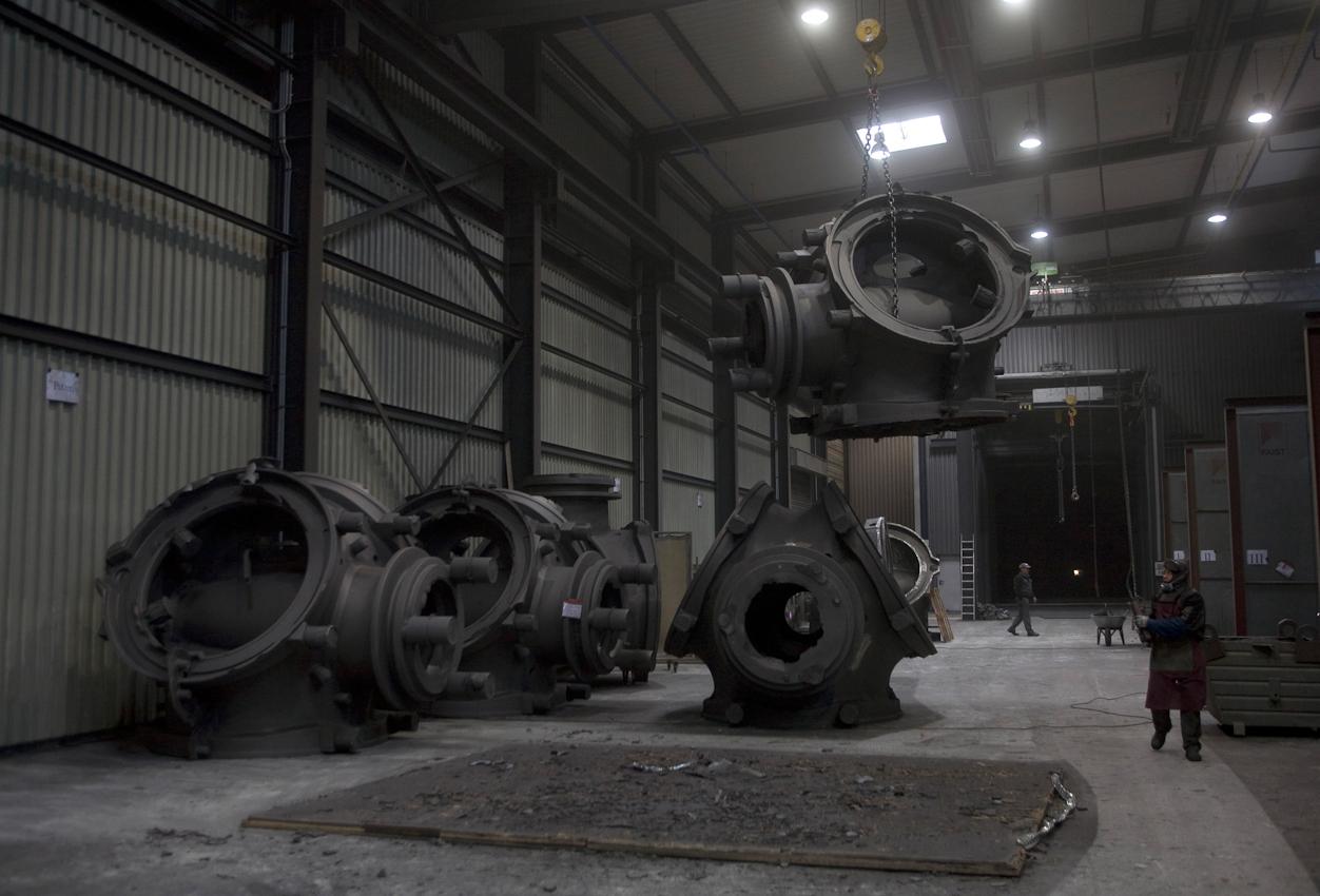 In der Bearbeitungshalle werden die Gussteile entgratet und geschliffen. Dann warten sie, bis sie in die Lackiererei weitertransportiert werden. Ein Arbeiter bringt das Windrad-Nabengehäuse ins Zwischenlager.