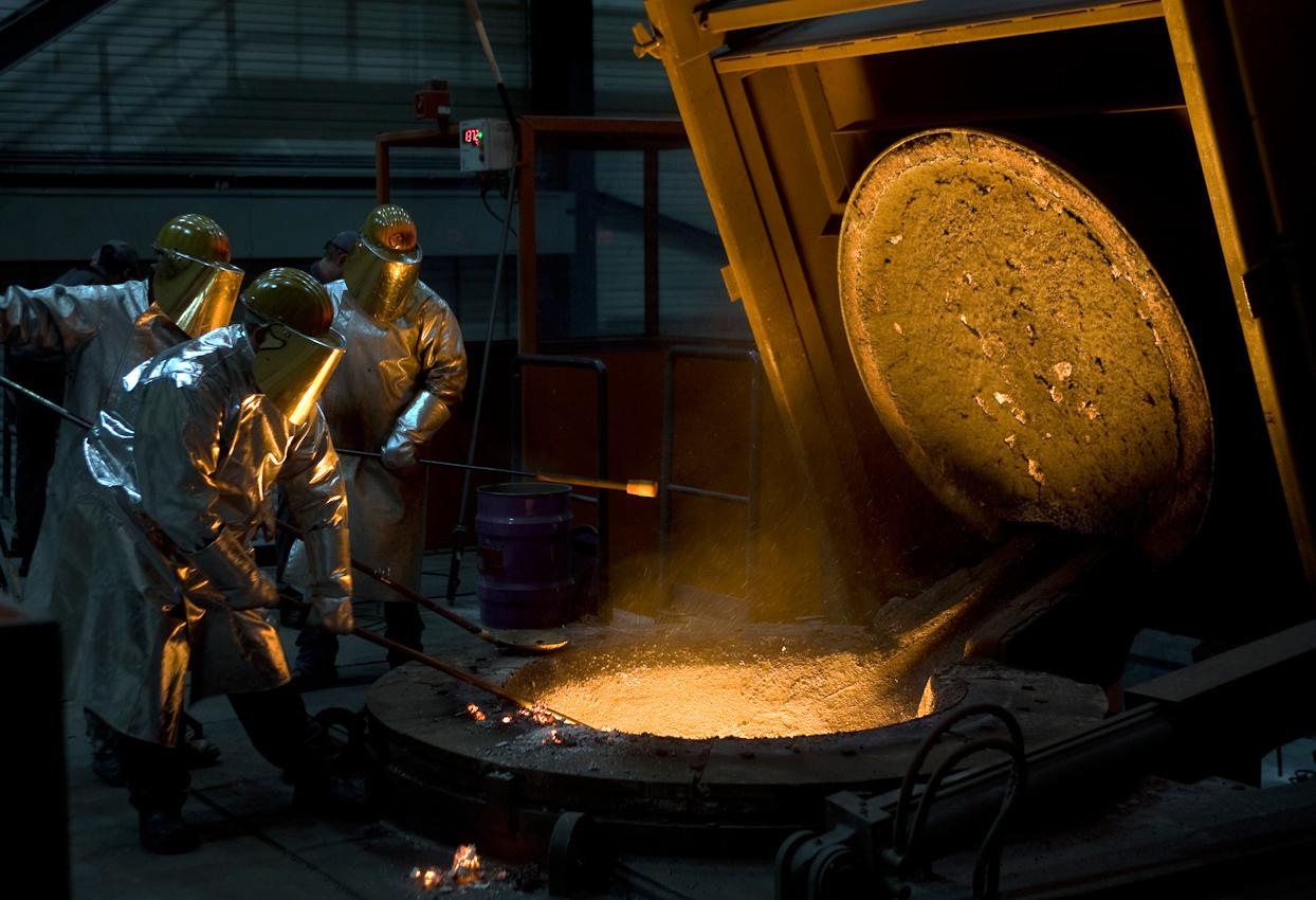 Die Schmelze ist in vollem Gange. Die Arbeiter am Ofen entfernen die Schlacke, die sich an der Oberfläche des Schmelzgutes sammelt. Hitzefeste Anzüge und beschichtete Visiere an den Helmen schützen vor der Hitze.