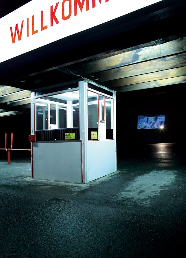 Das letzte Bild der Serie zeigt das Kassenhaus und die Zufahrt des Drive-In Autokinos in Köln Porz-Eil an der Rudolf-Diesel-Straße. Als ich am späten Abend des 7. Mai dort eintraf, ärgerte ich mich zunächst: aufgrund des Wetters war das Gittertor zu und die Anlage verwaist. Doch die Leuchtreklame war an und auch der Film lief stumm über die Leinwand des einsamen, nass-kalten nachtlichen Platzes. Im Gegensatz zu den anderen Bildern der Strecke ist dieser Arbeitsplatz leer. Doch diese Einsamkeit und Tristess gibt dem letzten Bild der Serie eine besondere Spannung und Melancholie und erzählt auch eine Geschichte des 7. Mai 2010.