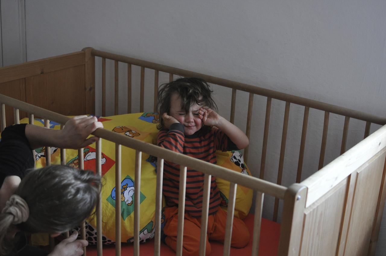 Der 3 Jahre alte Michael ist gerade aufgewacht. Er kniet noch in seinem Bett und reibt die Augen. Seine Mutter Maria fragt ihn, ob er gut geschlafen hat. Michael wohnt mit seiner Schwester Magdalena und seinen Eltern in Bayern in Garching an der Alz.